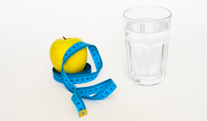 Image of a measuring tape, apple and glass of water